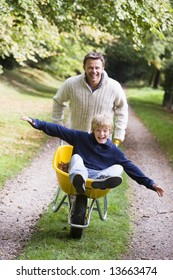 Man giving son ride in wheelbarrow on autumn path