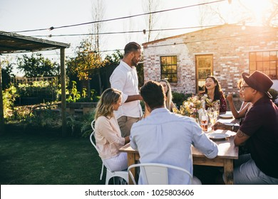 Man giving a speech to group of friends at party. Young people celebrating a special occasion sitting around a table in garden restaurant.