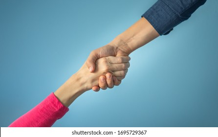 Man giving woman a helping hand isolated on blue background. Helping someone in need, charity, and friendship concept.