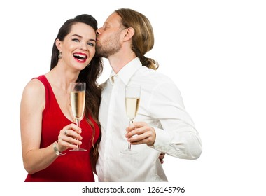 A man giving a woman a kiss on the cheek while having some champagne. Isolated on white.