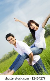 Man giving woman piggyback in meadow, laughing. Narrow focus on his eye.