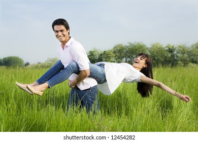 Man giving woman piggyback in meadow, laughing