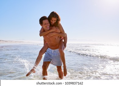 Man Giving Woman Piggyback On Summer Beach Vacation
