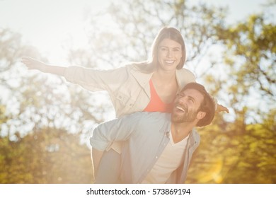 Man giving woman piggyback ride in park