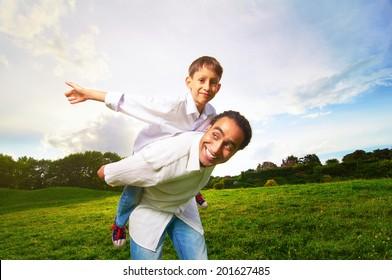 Man giving young boy piggyback ride outdoors smiling.