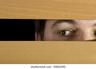 A man glances through the blinds