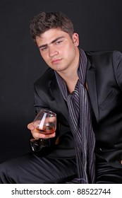 Man with glass of cognac on dark background