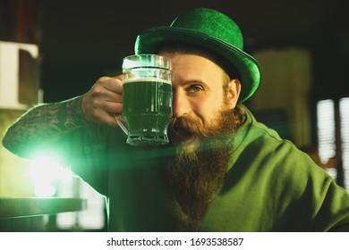 Man with glass of green beer in pub. St. Patrick's Day celebration