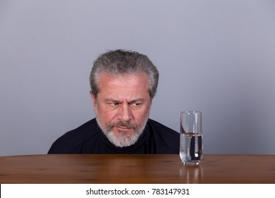 Man with glass half full, half empty, symbolic image