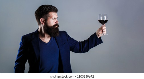 Man with a glass of red wine in his hands. Beard man, bearded, sommelier tasting red wine. Sommelier, degustator with glass of wine, winery, male winemaker. Man holding glass of champagne in hand.