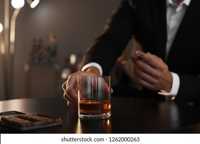 Man with glass of whiskey and cigar sitting at table, closeup. Space for text