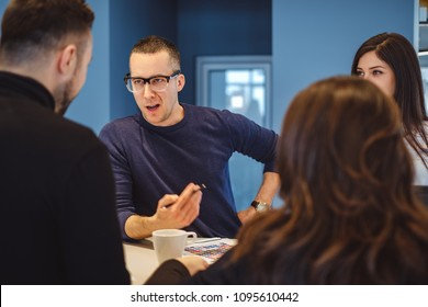 Man with glasses aggressively talking at the office meeting to his colleagues