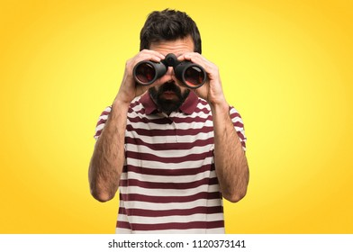 Man with glasses with binoculars on colorful background