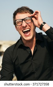 A man with glasses and black jacket laughs.