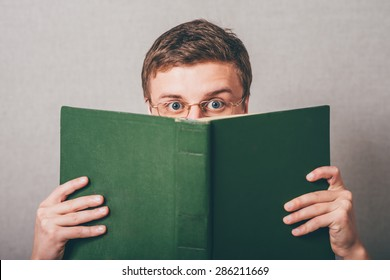 The man in glasses covered his face with a book. On a gray background.