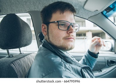 Man in glasses driving car look from inside