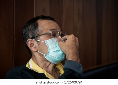Man in glasses fixing on his surgical mask holding the nose mask for protect Covid-19 or PM 2.5 dust and serious of the air pollution and wooden at home background, Male in glasses, Surgical mask,