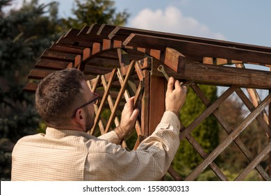 A man with glasses and a flannel shirt during spring gardening. Renovation and maintenance of garden pergolas. The man's hand tightens the screw with a wrench