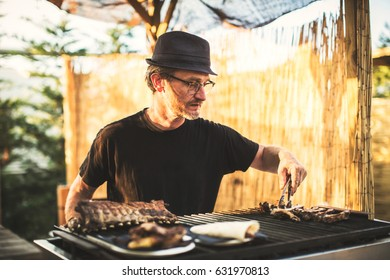 Man in glasses and hat roasting meat on grill outside.