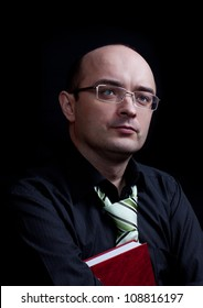 Man with glasses holding red book and looking above