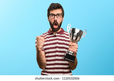 Man with glasses holding a trophy on colorful background
