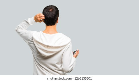 Man with glasses and listening music on back position looking back while scratching head on grey background