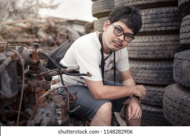 man with glasses in metal scrap junk yard surrounding with vehicle and engine parts, tires and metal scrap. He hold DSLR camera like foreigner tourist.