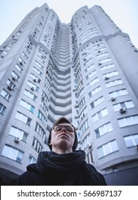Man in glasses on the background of high building, day , outdoor , low angle