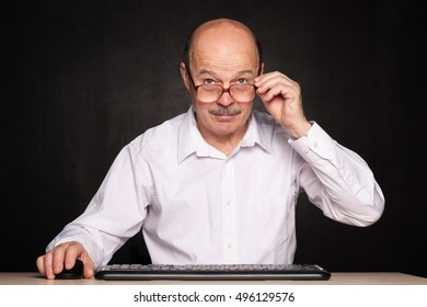 Man in glasses on the tip of nose types on keyboard and looks forward