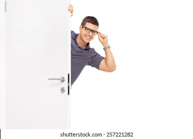 Man with glasses peeking behind a door isolated on white background