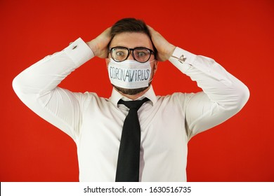 A man in glasses, a shirt and a mask with the inscription coronavirus in a panic holds his head. Coronavirus concept. Coronavirus epidemic.