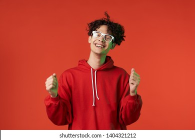 man in glasses is smiling on a red background