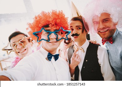 Man in glasses with stars smiles while standing with his gay friends. Smiling man in white wig stands with gays at a party.