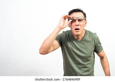 Man with glasses straining his eyes because he can't see well. Mid shot. White background.