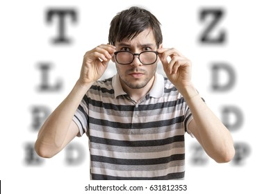 Man with glasses is testing his sight. Chart for eye sight testing in background.