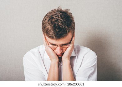 The man in glasses upset sad, hands on his cheeks, his head lowered. On a gray background.