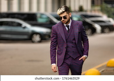 man in glasses and violet luxery three-piece suit, bow tie posing on the street