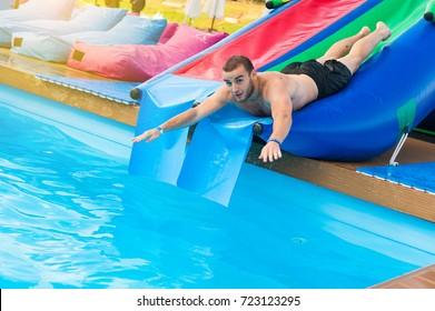 Man gliding in swimming pool on slide