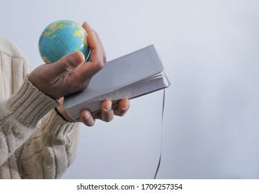 man with globe praying to god with hands together Caribbean man praying with white background stock photo