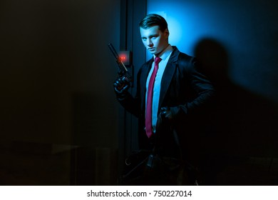 Man with gloves and a gun, he's a professional killer, his pistol with a silencer.