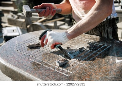 a man in gloves knocking on a chisel breaking a marble stone. stone worker. manufacturing of monuments. handwork