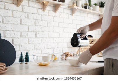 Man in gloves whipping egg whites with the electric mixer in the kitchen