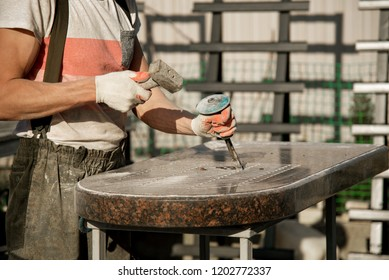 A man in gloves working with a hammer and chisel with a marble stone. manufacturing of monuments. work with marble. hard work