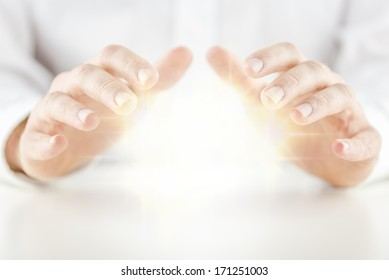 Man with a glowing crystal ball holding his hands protectively above it to feel the energy as he foretells or predicts the future conceptual of a fortune teller, soothsayer, mystic or clairvoyant