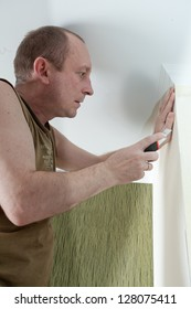the man glues wall-paper on wall