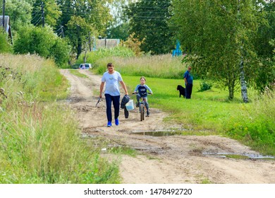 man goes fishing, holds a fishing rod in his hand, and a boy rides a bicycle on a dirt road on a sunny summer day. Tver, Russia August 2019