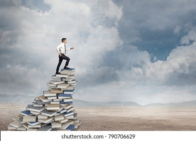 man goes up on books pile in the desert wisdom concept
