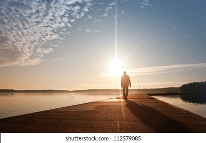 A man goes on the concrete pier in the sunrise