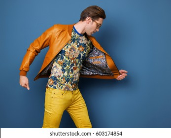 The man goes, runs in bright court and bright clothes with prints, yellow jeans and dark glasses. Blue background