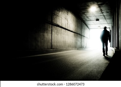 A man going to the end of a tunnel to the light. Silhouette of a man going to light in the end of a tunnel. Moving to the future.